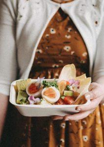 Foto zeigt Frau mit Essen in der Hand