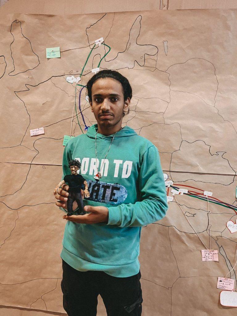 ZeigtMann mit Figur vor Landkarte