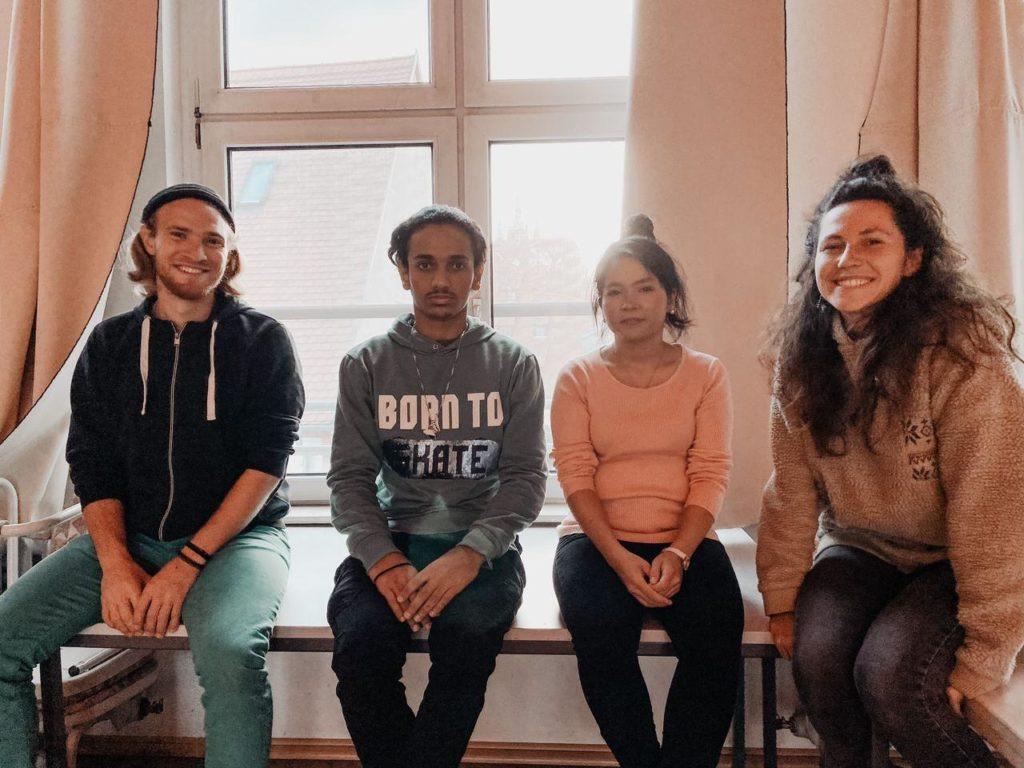 Vier Menschen sitzen vor Fenster und lächeln