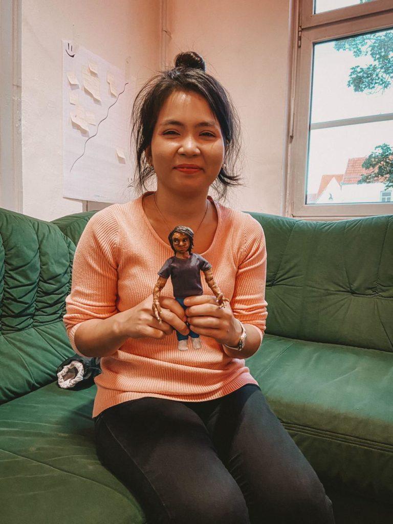 Zeigt Frau lächlend mit Puppe von sich selbst in der Hand