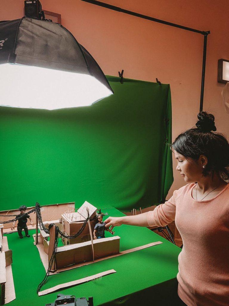 Frau mit Requisiten für Stop-Motion Film vor Greenscreen