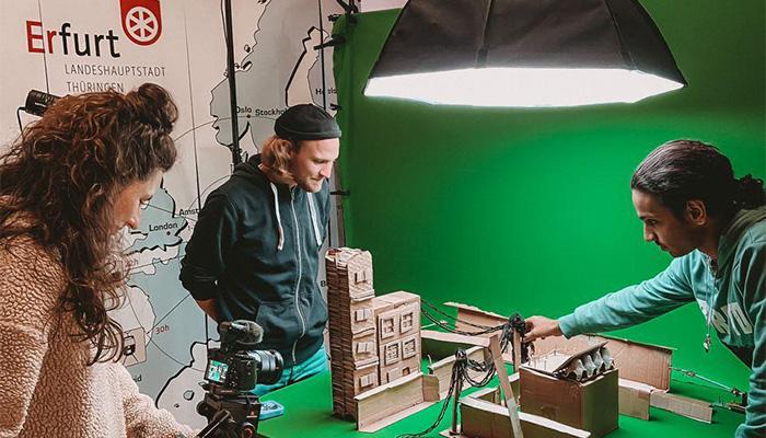 Zeigt drei Erwachsene bei Aufnahmen eines Stop-Motion Films vor Greenscreen